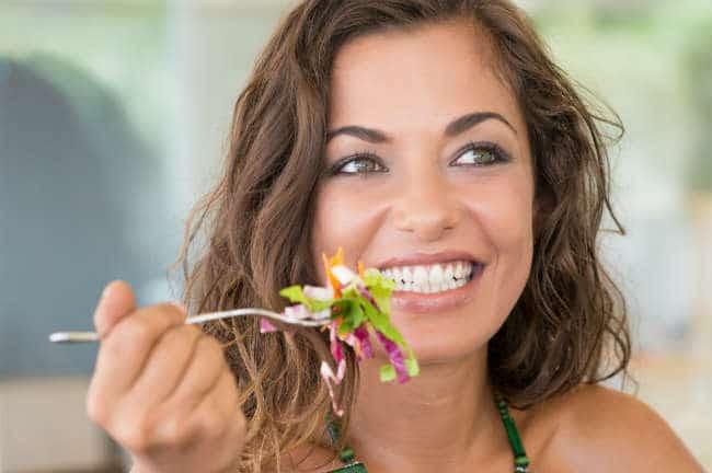 mujer-sonriente-comiendo-ensalada